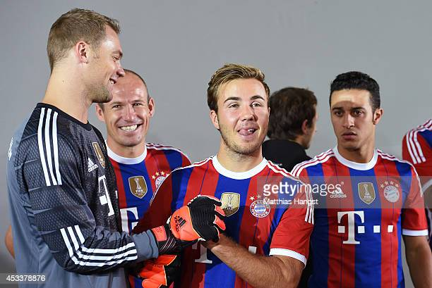 Goalkeeper Manuel Neuer of Muenchen jokes with Mario Goetze of Muenchen during the FC Bayern Muenchen Team Presentation at Saebener Strasse on August...