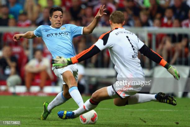 Goalkeeper Manuel Neuer of Muenchen makes a save against Samir Nasri of Manchester during the Audi Cup Final match between FC Bayern Muenchen and...