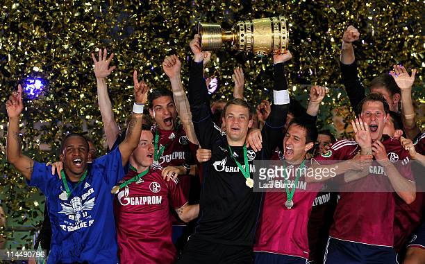 Goalkeeper Manuel Neuer of Schalke lifts the trophy after winning the DFB Cup final match between MSV Duisburg and FC Schalke 04 at Olympic Stadium...