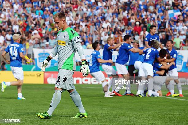 Goalkeeper MarcAndre ter Stegen of Moenchengladbach leaves the pitch as players of Darmstadt celebrate after the DFB Cup first round match between...
