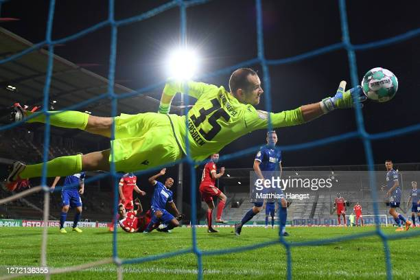 Goalkeeper Marius Gersbeck of Karlsruhe fails to save a shot from Nico Schlotterbeck of Berlin who scores his team's extra time winning goal during...