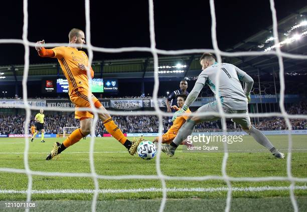 Goalkeeper Marko Maric and Aljaz Struna of Houston Dynamo let in a goal by Gadi Kinda of Sporting Kansas City during the game at Children's Mercy...