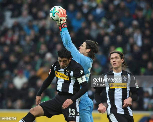 Goalkeeper Marvin Hitz of Augsburg catches the ball and Lars Stindl of Moenchengladbach and Jannik Vestergaard in action during the Bundesliga match...