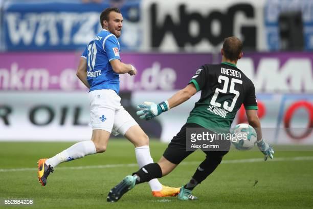 Goalkeeper Marvin Schwaebe of Dresden makes a save against Kevin Grosskreutz of Darmstadt during the Second Bundesliga match between SV Darmstadt 98...