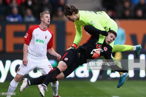 Goalkeeper Marwin Hitz of Augsburg falls over Luka Jovic of Frankfurt during the Bundesliga match between FC Augsburg and Eintracht Frankfurt at...
