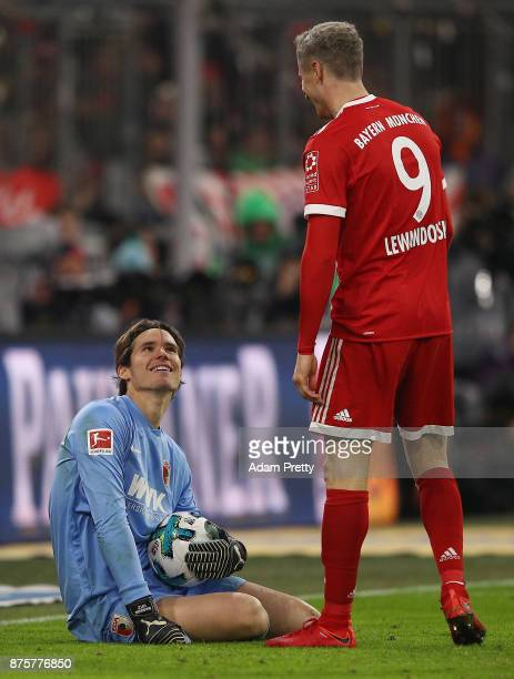 Goalkeeper Marwin Hitz of Augsburg smiles at Robert Lewandowski of Bayern Muenchen during the Bundesliga match between FC Bayern Muenchen and FC...
