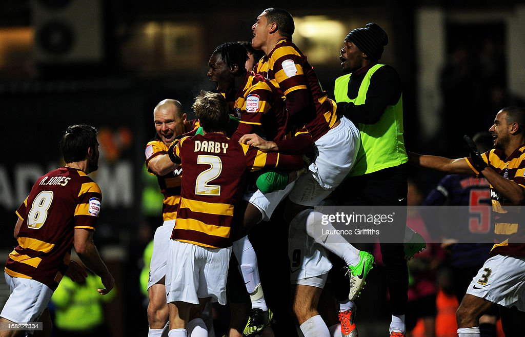 Goalkeeper Matt Duke (obscured) of Bradford is congratulated by teammates after saving penalty durinhg the shootout to win the Capital One Cup quarter final match between Bradford City and Arsenal at the Coral Windows Stadium, Valley Parade on December 11, 2012 in Bradford, England.