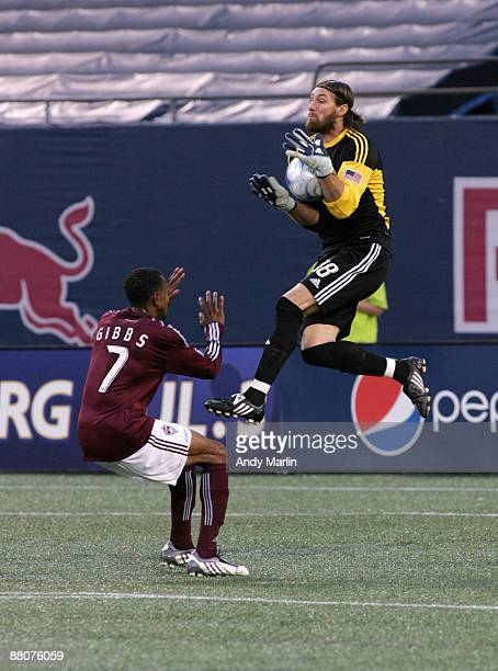 Goalkeeper Matt Pickens of the Colorado Rapids jumps high in the air to make as save as his teammate Cory Gibbs looks on during their game at Giants...