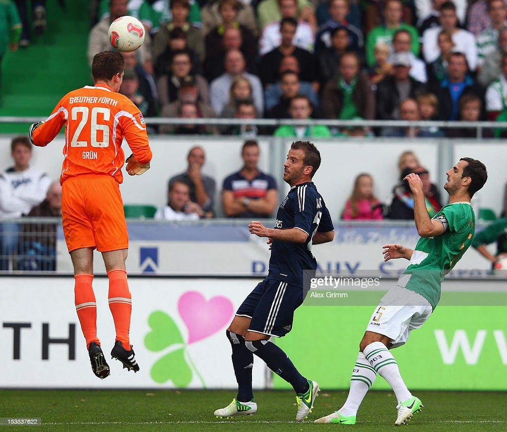 Goalkeeper Max Gruen of Greuther Fuerth clears the ball ahead of Rafael van der Vaart of Hamburg and team mate Mergim Mavraj during the Bundesliga match between SpVgg Greuther Fuerth and Hamburger SV at Trolli-Arena on October 6, 2012 in Fuerth, Germany.