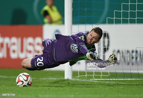 Goalkeeper Max Gruen of Wolfsburg saves the decisive penalty of Milan Ivana of Darmstadt in the shootout during the DFB Cup first round match between...
