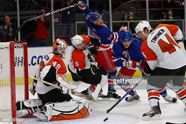 Goalkeeper Michael Leighton of the Philadelphia Flyers and team mate Kimmo Timonen defend a shot at goal by the New York Rangers during their game on...