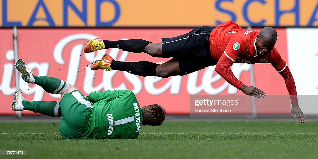 Goalkeeper Michael Ratajczak (L) of Duisburg saves the ball as Jose Vunguidica (R) of Wiesbaden misses a chance at goal during the 3. Liga match between MSV Duisburg and SV Wehen Wiesbaden at Schauinsland-Reisen-Arena on March 1, 2014 in Duisburg, Germany.
