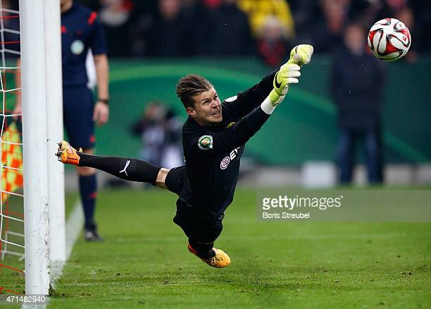 Goalkeeper Mitchell Langerak of Dortmund saves a penalty during the penalty shoot-out of the DFB Cup semi final match between FC Bayern Muenchen and...