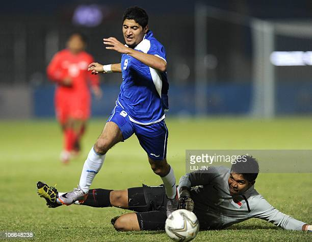 Goalkeeper Mohamad Izwan Mahbud of Singapore challenges Khudhair Abdulhadi of Kuwait during their men's group D pool football match at the 16th Asian...