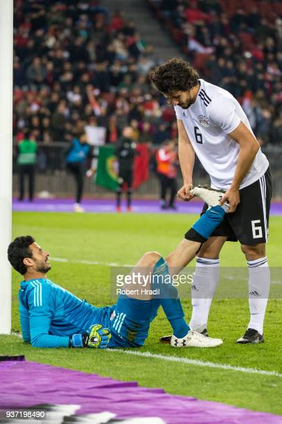 Goalkeeper Mohamed ElShenawy of Egypt getting help from his teammate Ahmed Hegazi to stretch his left leg during the International Friendly between...