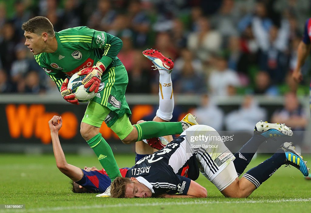 Goalkeeper Nathan Coe of the Victory makes a save as Nicholas Ansell (R) of the Victory and Ryan Griffiths of the Jets compete for the ball during the round 13 A-League match between the Melbourne Victory and the Newcastle Jets at AAMI Park on December 28, 2012 in Melbourne, Australia.