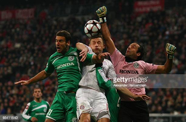 Goalkeeper Nir Davidovitch and Dekel Keinan of Haifa battle for the ball with Ivica Olic of Bayern Muenchen during the UEFA Champions League Group A...
