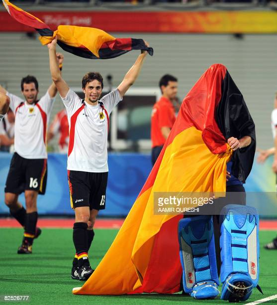 Goalkeeper of Germany's Max Whinhold wears national flags as he celebrates with teammates Tobias Hauke after winning the final against Spains of the...