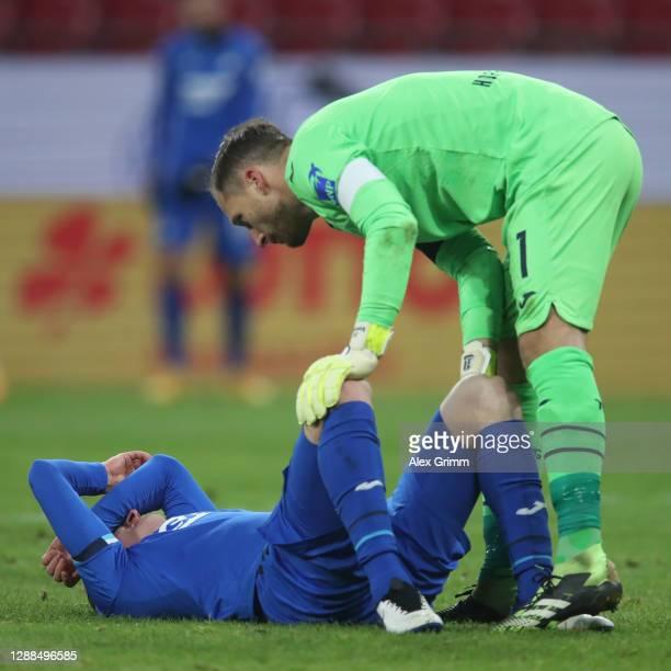 Goalkeeper Oliver Baumann of Hoffenheim looks after teammate Sebastian Rudy during the Bundesliga match between 1. FSV Mainz 05 and TSG Hoffenheim at...