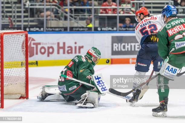 Goalkeeper Olivier Roy of Augsburger Panther, Patrick Hager of EHC Red Bull Muenchen and Patrick McNeill of Augsburger Panther battle for the ball...