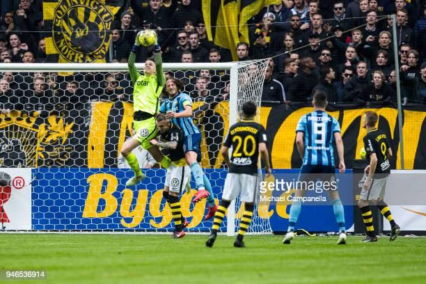 AIK goalkeeper Oscar Linner makes a save as teammate Alexander Milosevic collides with Jonas Olsson of Djurgardens IF during an Allsvenskan match...