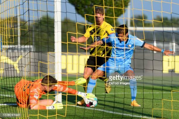 Goalkeeper Patrick Drewes of VfL Bochum, Lukasz Piszczek of Borussia Dortmund and Cristian Gamboa of VfL Bochum battle for the ball during the...
