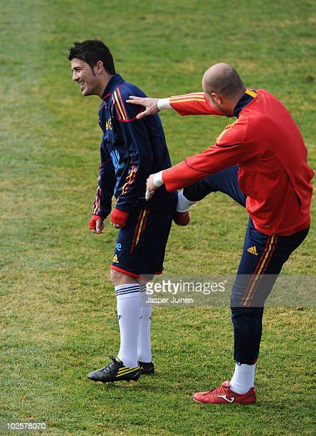 Goalkeeper Pepe Reina of Spain jokes with his teammate David Villa during a training session ahead of their World Cup 2010 QuarterFinal match against...