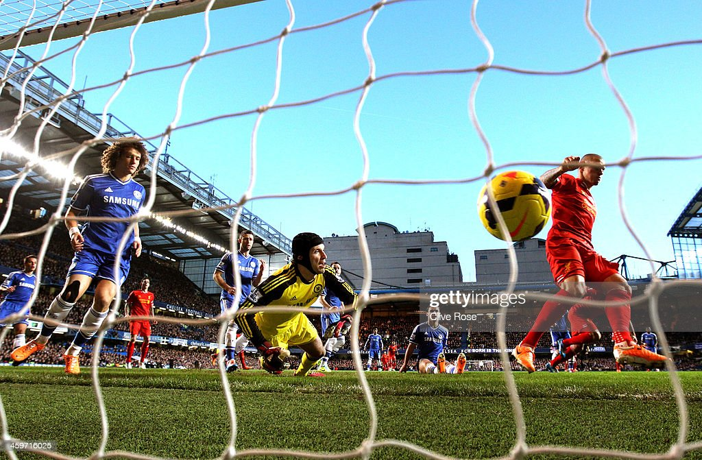 Goalkeeper Petr Cech of Chelsea dives at the ball as Martin Skrtel (R) of Liverpool scores the opening goal during the Barclays Premier League match between Chelsea and Liverpool at Stamford Bridge on December 29, 2013 in London, England.