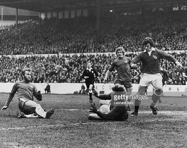 QPR goalkeeper Phil Parkes is covered by team mate Tony Hazell as he stops a shot from Chelsea player Tommy Baldwin during a third round FA Cup match...