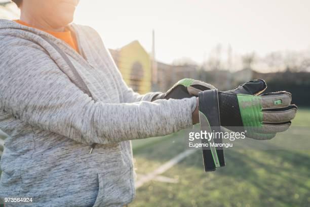 goalkeeper putting on gloves - torhüter stock-fotos und bilder