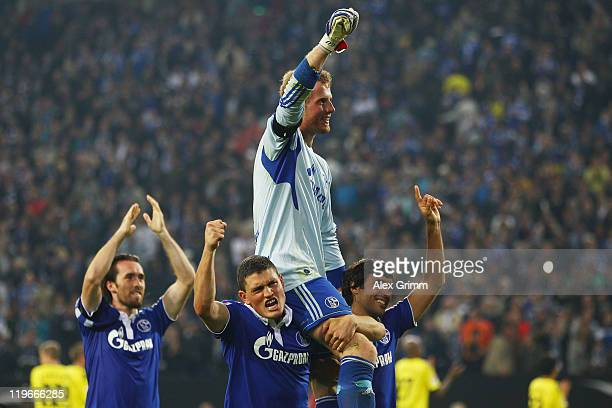 Goalkeeper Ralf Faehrmann of Schalke celebrates with team mates Christian Fuchs Kyriakos Papadopoulos and Raul after winning the Supercup match...