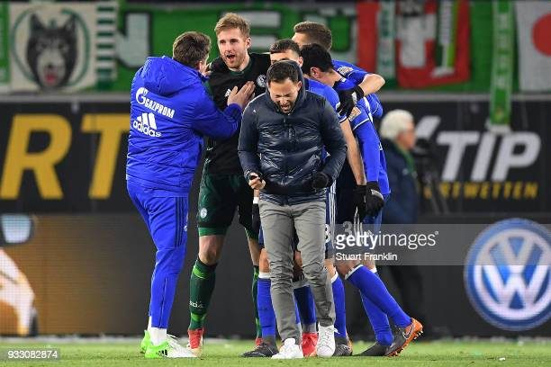 Goalkeeper Ralf Faehrmann of Schalke is celebrated by players of officials of Schalke while coach Domenico Tedesco of Schalke reacts after the...