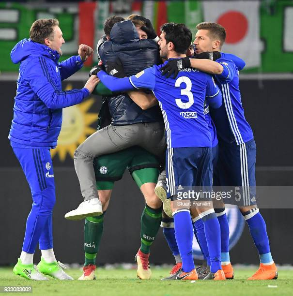 Goalkeeper Ralf Faehrmann of Schalke is embraced by Coach Domenico Tedesco of Schalke and other players of Schalke in celebration after the...