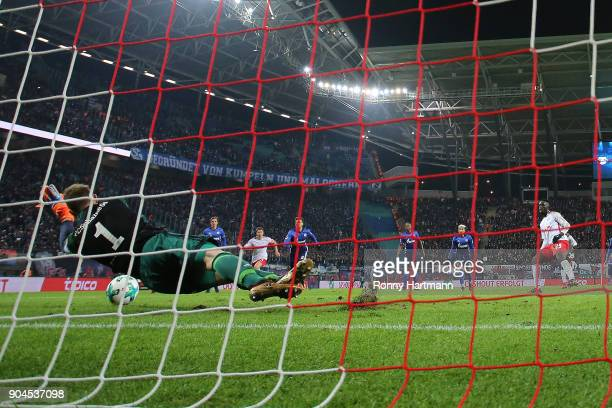 Goalkeeper Ralf Faehrmann of Schalke saves a penalty against JeanKevin Augustin of Leipzig during the Bundesliga match between RB Leipzig and FC...