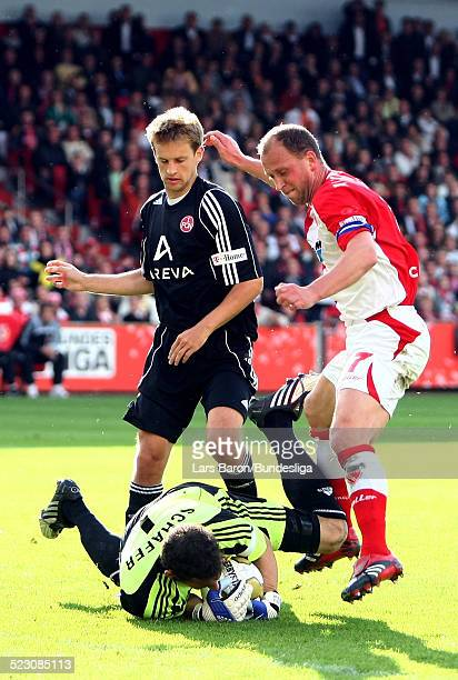 Goalkeeper Raphael Schaefer of Nuernberg catches the ball infront of Timo Rost of Cottbus during the Bundesliga Play Off match between FC Energie...