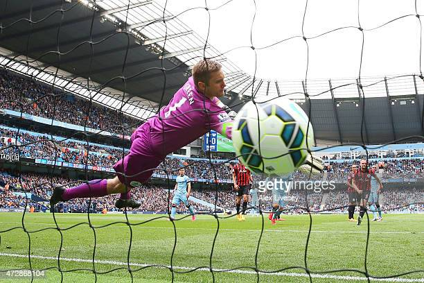 Goalkeeper Robert Green of QPR dives in vain as Aleksandar Kolarov of Manchester City scores his team's second goal from a kick during the Barclays...