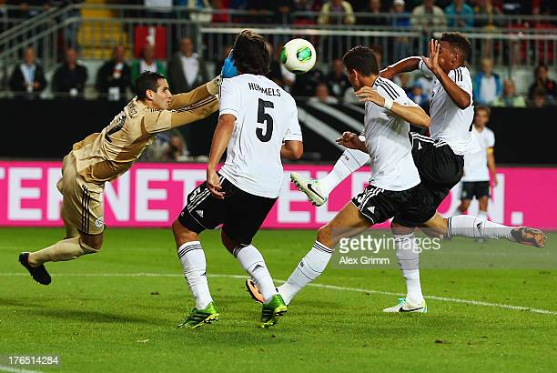 Goalkeeper Roberto Fernandez of Paraguay makes a save against Mats Hummels Mario Gomez and Jerome Boateng of Germany during the international...
