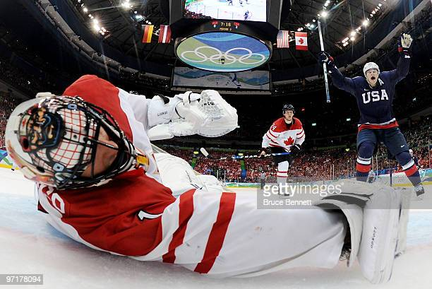 Goalkeeper Roberto Luongo of Canada dives in vain as Ryan Kesler scores his team's opening goal during the ice hockey men's gold medal game between...