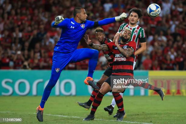 Goalkeeper Rodolfo of Fluminense clears the ball against Gabriel Barbosa of Flamengo during a match between Flamengo and Fluminense as part of State...