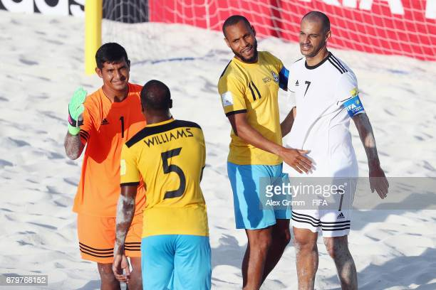Goalkeeper Rolando Gonzalez and Madjer of FIFA All Stars shake hands with Kyle Williams and Gavin Christie of Bahamas after the FIFA Beach Soccer...