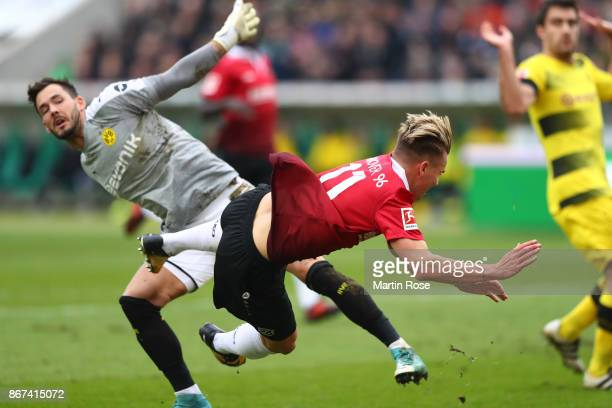 Goalkeeper Roman Buerki of Dortmund fouls Felix Klaus of Hannover which leads to a penalty for Hannover during the Bundesliga match between Hannover...