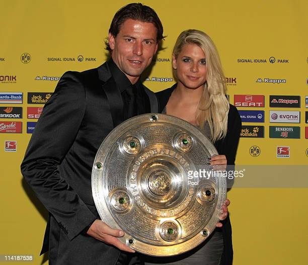 Goalkeeper Roman Weidenfeller and his girlfriend Lisa pose with the German Championship trophy during the dinner to celebrate their German Bundesliga...
