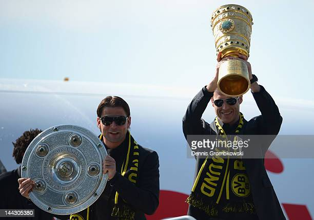Goalkeeper Roman Weidenfeller of Dortmund and teammate Sebastian Kehl present the Bundesliga and DFB Cup trophies during the team's arrival at...