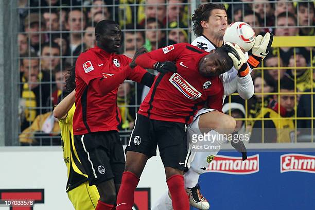 Goalkeeper Roman Weidenfeller of Dortmund is challenged by Cedric Makiadi and Papiss Demba Cisse of Freiburg during the Bundesliga match between SC...