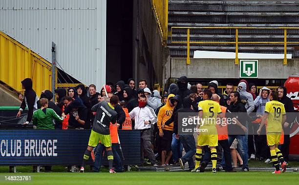 Goalkeeper Roman Weidenfeller, Sebastian Kehl and Kevin Grosskreutz trie to stop fans of Dortmund, who entered the pitch during a friendly match...