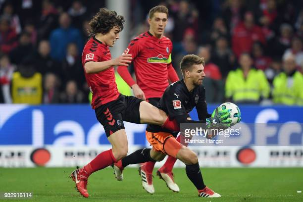 Goalkeeper RonRobert Zieler of Stuttgart is challenged by Caglar Souyuencue and Nils Petersen of Freiburg during the Bundesliga match between...