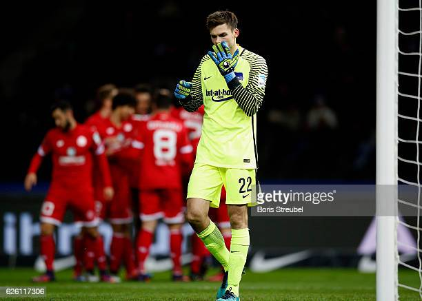 Goalkeeper Rune Jarstein of Hertha BSC looks dejected after Aaron Seydel of 1 FSV Mainz 05 celebrates with team mates his team's first goal during...
