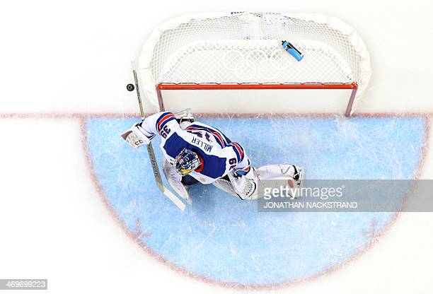 US goalkeeper Ryan Miller deflects the puck during the Men's Ice Hockey Group A match between Slovenia and USA at the Shayba Arena during the Sochi...