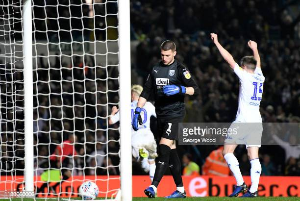 Goalkeeper Sam Johnstone of West Bromwich Albion stands dejected as Ezgjan Alioski of Leeds United runs of to celebrate scoring his sides fourth goal...