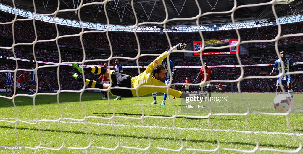 Goalkeeper Scott Carson of Wigan Athletic fails to stop the shot from Robin van Persie of Manchester United during the FA Community Shield match between Manchester United and Wigan Athletic at Wembley Stadium on August 11, 2013 in London, England.